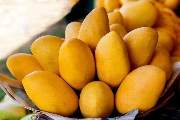 Stand del festival del mango con frutti di mango gialli freschi nel mercato di strada