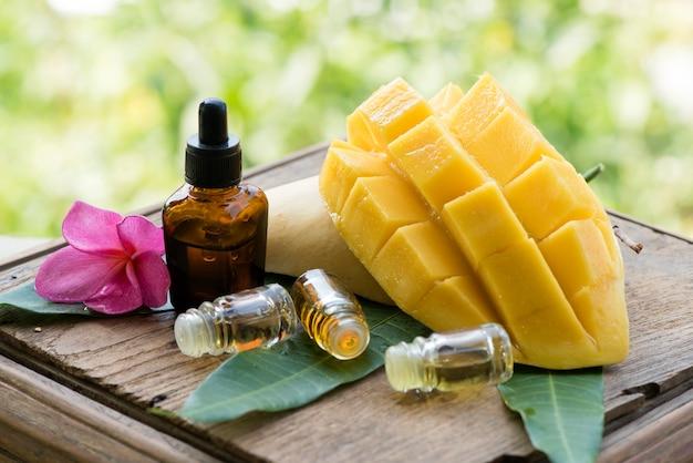 Frutto di mango e olio essenziale sul fondo della natura.