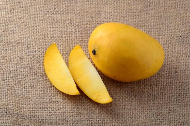 Frutto di mango con fetta su sfondo di stoffa di sacco