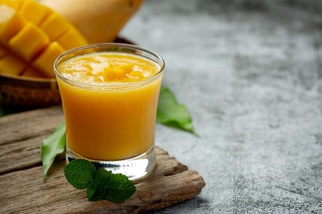 Succo di mango nel bicchiere sulla superficie scura