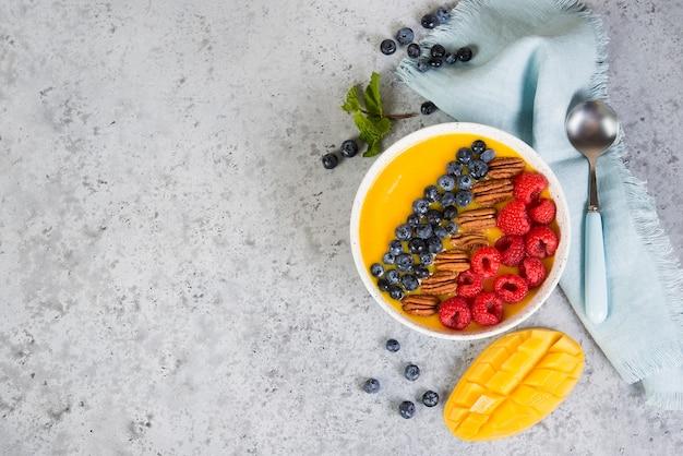 Ciotola di frullato di mango e arancia con frutti di bosco freschi e noci.