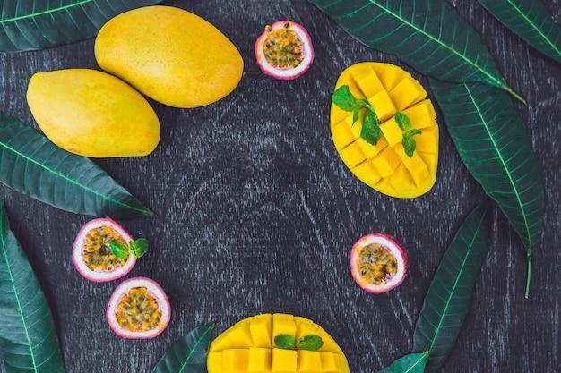 Mango e frutto della passione su un vecchio sfondo di legno. copia spazio.