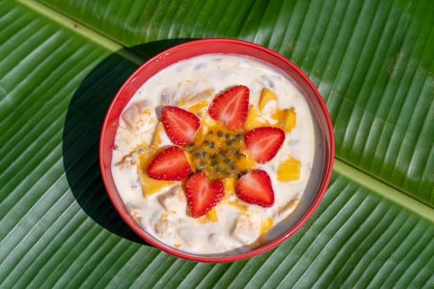 Mango, frutto della passione, fragola rossa e yogurt brulée. dessert di frutta a colazione con spicchi di mango e fragola perfettamente maturi di stagione, polpa di frutto della passione fresca ricoperta, primo piano