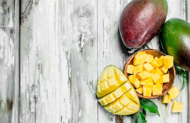 I pezzi di mango in una ciotola e un intero mango. sullo sfondo di legno