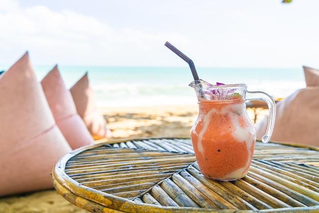 Barattolo di frullati di mango, ananas, anguria e yogurt o yogurt con sfondo di spiaggia di mare