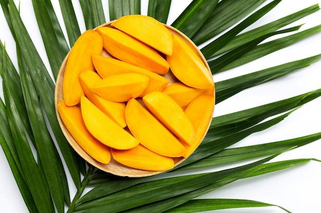 Fette di mango sul piatto di legno su foglie di palma tropicale.