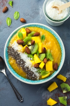 Ciotola per frullato di mango con pezzi di kiwi, mango, scaglie di cocco e semi di chia su una pietra