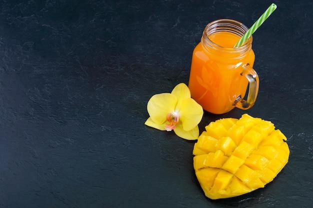 Frullato di mango in un barattolo di vetro e mango fresco su uno sfondo nero. frullato di mango. concetto di frutta tropicale.