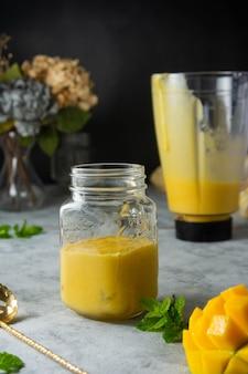 Frullato di mango in barattolo di vetro con frutta fresca di mango e menta, sfondo scuro