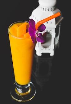 Frullato di mango in vetro lungo e fiore di orchidea con sfondo nero.