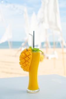 Bicchiere di frullati di mango con sfondo di spiaggia di mare