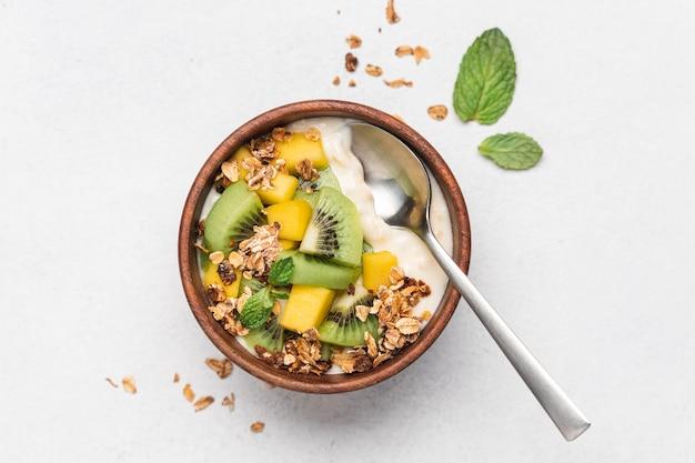 Yogurt al mango con muesli e kiwi in una ciotola di legno su sfondo bianco.