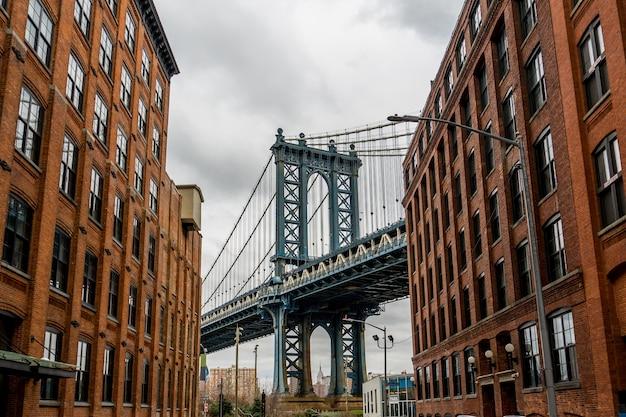 Manhattan bridge visto da dumbo, brooklyn, new york tra due edifici di mattoni rossi