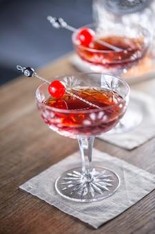 Cocktail classico manhattan come aperitivo short drink con whisky, vermouth, bitter aromatico angostura e guarnizione di ciliegia.