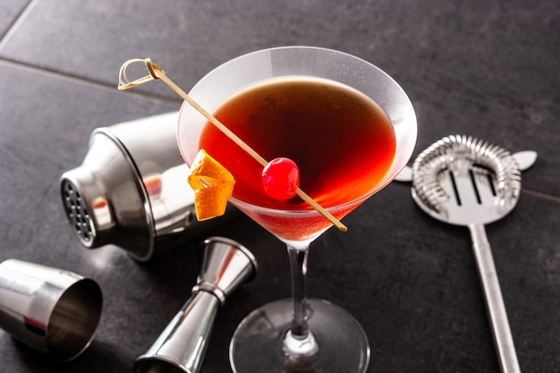 Cocktail di manhattan con la ciliegia sulla tavola nera
