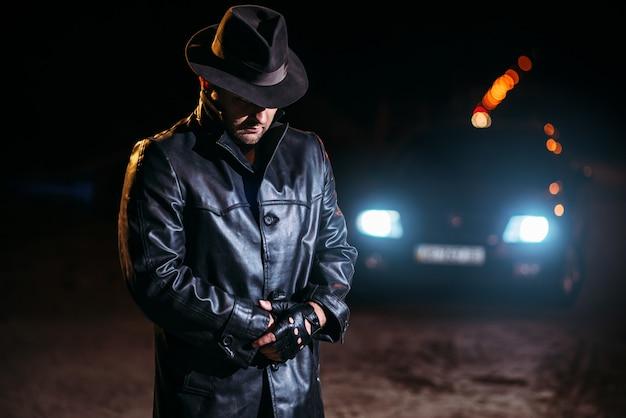 Maniaco in cappotto di pelle nera e cappello, vista posteriore