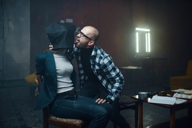 Il rapitore maniaco lecca la sua vittima femminile con un sacchetto in testa. il rapimento è un crimine grave, pazzo psicopatico maschio, rapimento horror, violenza