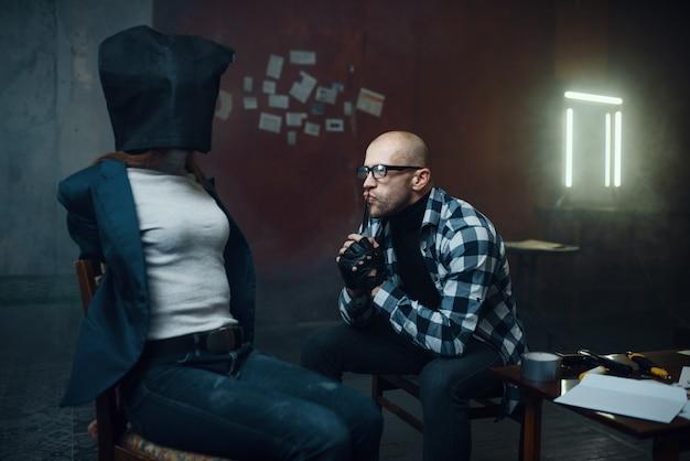Il rapitore maniaco guarda la sua vittima femminile con una borsa in testa. il rapimento è un crimine grave, pazzo psicopatico maschio, rapimento horror, violenza