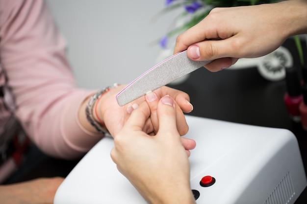 Manicure nel salone di bellezza. messa a fuoco selettiva sulle unghie del cliente