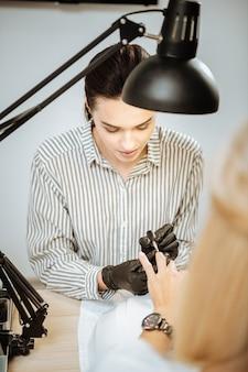 Manicure per imprenditrice. vista dall'alto del giovane artista dai capelli scuri che fa manicure per imprenditrice