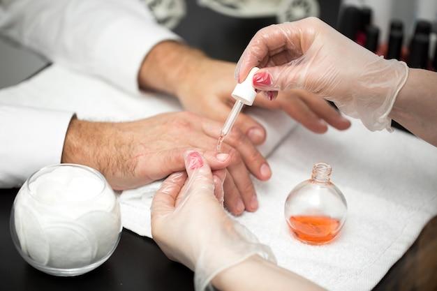 Manicure, mani spa olio per cuticole. primo piano delle mani dell'uomo bello. unghie curate. mani di bellezza. trattamento di bellezza.