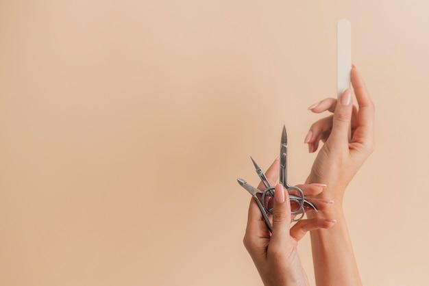 Manicure cura sana tenendo gli strumenti per unghie