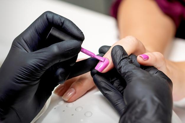 Maestro di manicure che applica smalto rosa all'unghia femminile nel salone di bellezza