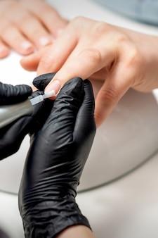 Il maestro del manicure sta applicando la vernice trasparente sulle unghie femminili nel salone del chiodo
