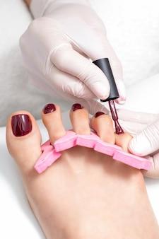 Il maestro di manicure sta dipingendo sulle unghie dei piedi femminili con smalto marrone rossiccio a pennello indossando guanti bianchi