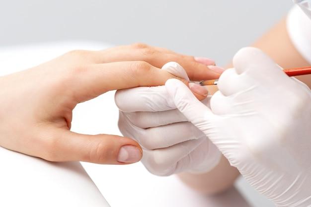 Maestro di manicure in guanti di gomma che applica smalto trasparente sulle unghie femminili nel salone di bellezza