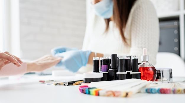 Maestro di manicure in guanti di gomma e maschera a parlare con il cliente nell'interiore di studio di bellezza