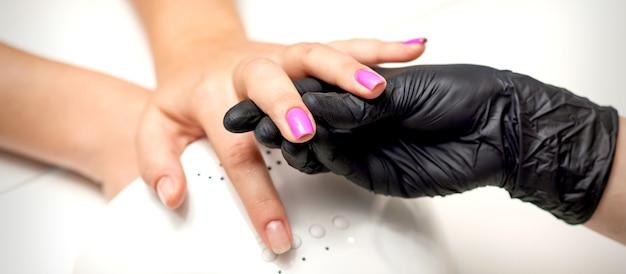 La mano del maestro di manicure tiene un dito femminile con smalto viola mentre dipinge le unghie in un salone di bellezza