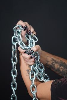 Manicure le unghie delle mani che tengono la catena