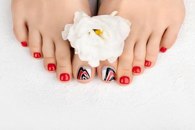 Manicure, concetto di salone di bellezza pedicure. piedi di donna su sfondo grigio