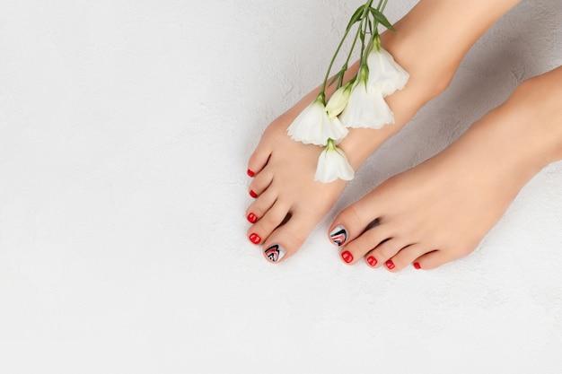 Manicure, concetto di salone di bellezza pedicure. piedi di donna su grigio