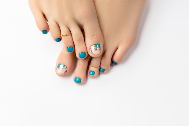 Manicure, concetto di salone di bellezza pedicure. piedi di donna su sfondo bianco. bellissimo design per unghie turchese estivo.