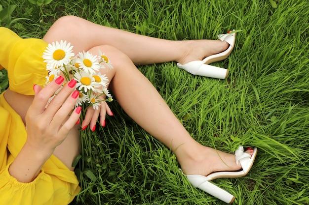 Manicure e pedicure con top coat corallo sulle unghie con bouquet di margherite sulla ragazza che si siede sull'erba in estate.