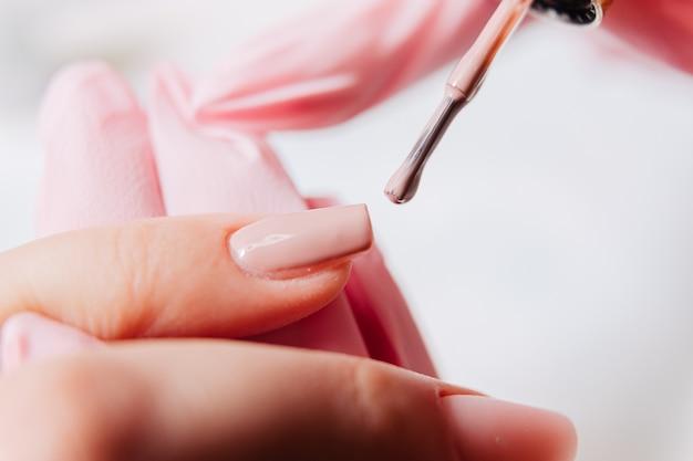 Processo di manicure. il manicure dipinge le unghie. smalto per unghie.