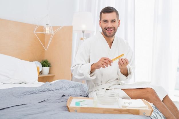 Strumenti per manicure. allegro bell'uomo utilizzando una lima per unghie mentre si prende cura della sua manicure