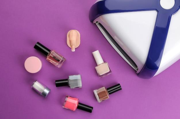 Manicure. lampada uv e smalto per unghie su uno sfondo viola alla moda. accessori per manicure e strumenti per le unghie. vista dall'alto