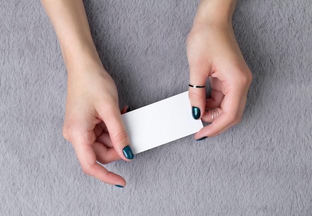 Le mani della donna curata che tengono biglietto da visita sulla tavola simile a pelliccia grigia