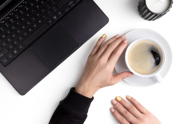Le mani della donna curata che tengono tazza di caffè su un posto di lavoro