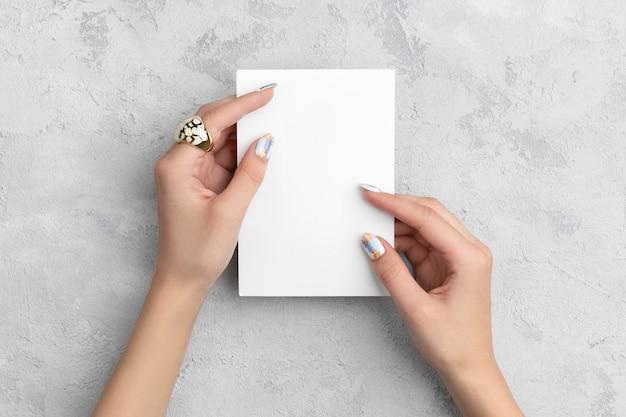 Le mani della donna curata che tengono cartolina sulla tavola di cemento grigia