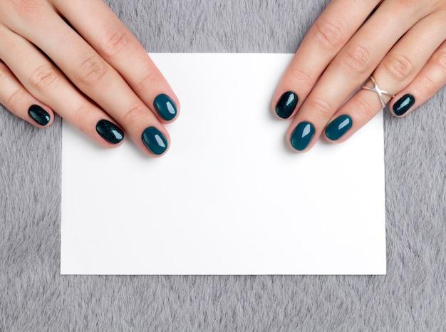 Le mani della donna curata che tengono cartolina sulla tavola simile a pelliccia grigia