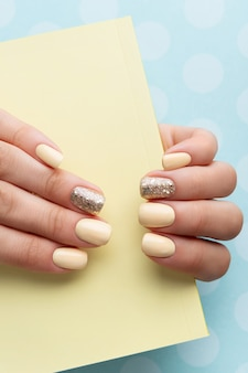 Mani della donna curate con manicure gialla alla moda in stile minimal.