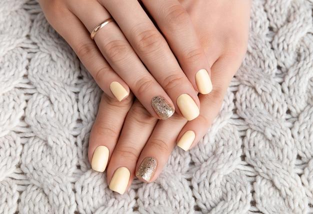 Mani della donna curate con maglione beige caldo della lana.
