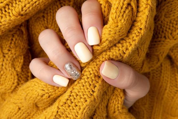 Mani della donna curate con maglione giallo caldo della lana.