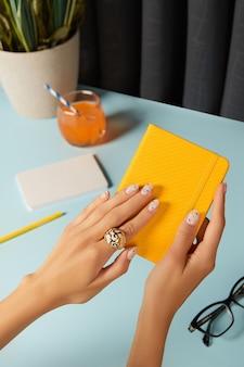 Mani della donna ben curate che tengono il blocco note sul tavolo blu