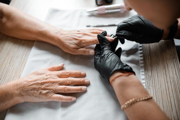 Estetista facendo cura delle unghie a una donna anziana, primo piano