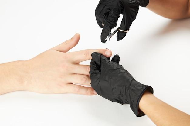Manicure durante il lavoro utilizzando le forbici per manicure. un processo di manicure da uomo. una persona caucasica irriconoscibile che fa servizio di unghie al salone spa. bellezza maschile e assistenza sanitaria
